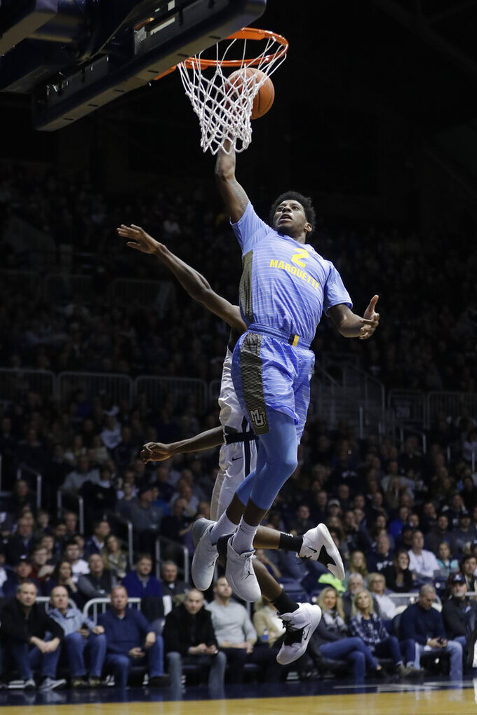 Marquette's Sacar Anim (2) goes up for a dunk against Butler's Kamar Baldwin during the second half of an NCAA college basketball game, Wednesday, Jan. 30, 2019, in Indianapolis. Marquette won 76-58. (AP Photo/Darron Cummings)