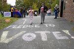 People walk past writing on the sidewalk ahead of an