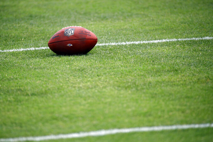 FILE - In this July 28, 2017, file photo, a football sits on a Baltimore Ravens practice field during NFL football training camp in Owings Mills, Md. As teams adhere to the medical protocols that wisely and necessarily have been ordered by the league and the players' union, any sort of football action might be delayed until mid-August. (AP Photo/Patrick Semansky, File)