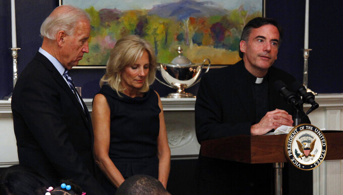 FILE - In this Nov. 22, 2010, file photo, Vice President Joe Biden, left, and his wife, Jill Biden, center, stand with heads bowed as the Rev. Kevin O'Brien says the blessing during a Thanksgiving meal for Wounded Warriors in Washington. O'Brien, the Jesuit priest who presided over an inaugural Mass for President Joe Biden, is under investigation for unspecified allegations and is on leave from his position as president of Santa Clara University in Northern California, according to a statement from the college's board of trustees. (AP Photo/Carolyn Kaster, File)