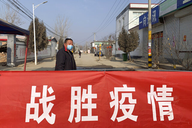A man wearing a face mask stands near a banner reading
