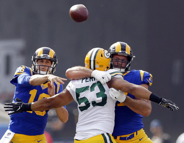 FILE - In this Oct. 28, 2018, file photo, Los Angeles Rams quarterback Jared Goff, left, throws a pass as offensive tackle Andrew Whitworth, right, blocks Green Bay Packers' Nick Perry (53) during the first half of an NFL football game in Los Angeles. Not many offensive linemen in NFL history can match Whitworth's high-level longevity — not even those who dominated the left tackle position when Whitworth was coming up. (AP Photo/Marcio Jose Sanchez, File)