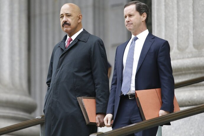 Ted Wells, Jr., left, the lead attorney for Exxon, leaves Manhattan Supreme court with a colleague Thursday, Nov. 7, 2019, in New York.  New York's attorney general is accusing Exxon Mobil of misleading investors about how profitable the company will remain as governments impose stricter regulations to combat global warming. (AP Photo/Frank Franklin II)