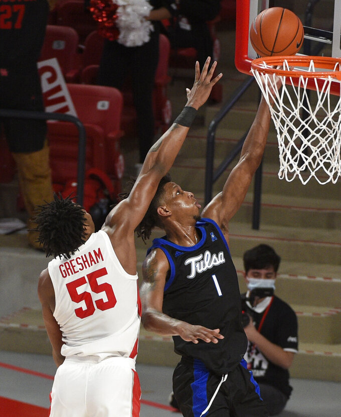 Tulsa guard Brandon Rachal (1) shoots as Houston forward Brison Gresham (55) defends during the second half of an NCAA college basketball game Wednesday, Jan. 20, 2021, in Houston. (AP Photo/Eric Christian Smith)