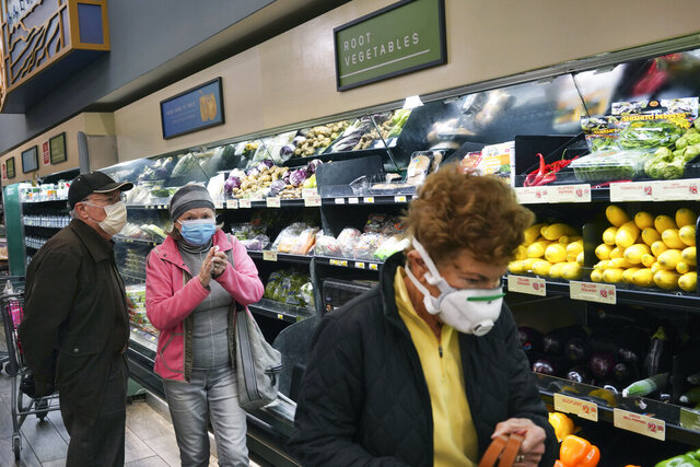 FILE - In this March 20, 2020, file photo, customers wear protective masks while shopping for groceries in the Sherman Oaks section of Los Angeles. Los Angeles Mayor Eric Garcetti has recommended that the city's 4 million people wear masks when going outside amid the spreading coronavirus. (AP Photo/Richard Vogel, File)