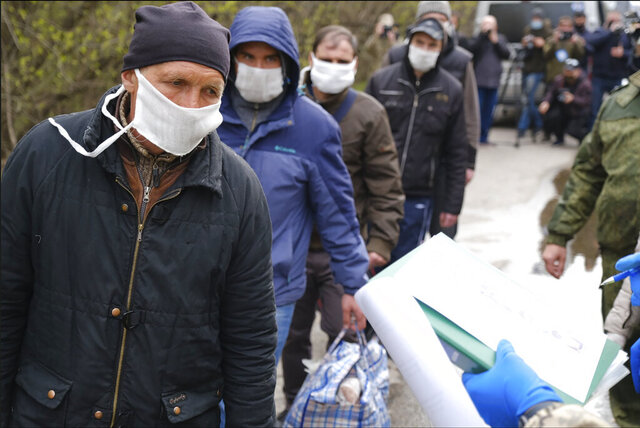 Russia-backed separatists war prisoners wearing masks to protect against coronavirus walk during a prisoner exchange, in Donetsk region, eastern Ukraine, Thursday, April 16, 2020. Ukrainian forces and Russia-backed rebels in eastern Ukraine have begun exchanging prisoners in a move aimed at ending their five-year long war. (Ukrainian Presidential Press Office via AP)