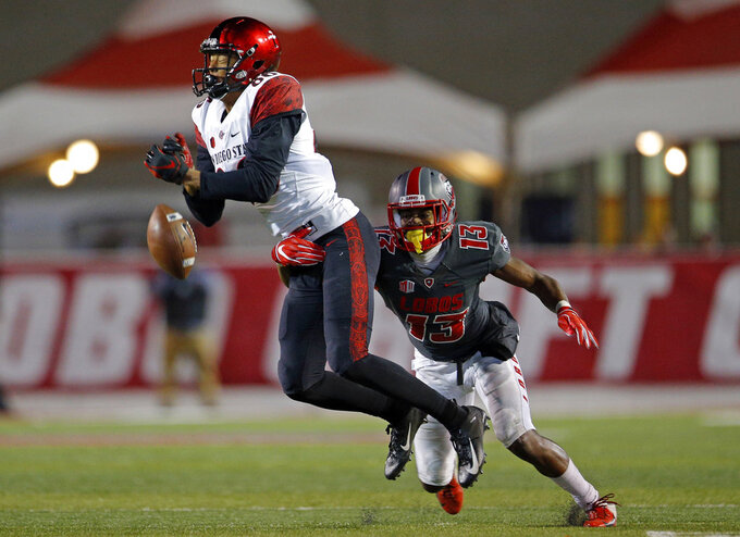 San Diego State wide receiver Isiah Macklin, left, misses a reception as he's defended by New Mexico cornerback Jalin Burrell (13) during the second half of an NCAA college football game in Albuquerque, N.M., Saturday, Nov. 3, 2018. San Diego State won 31-23. (AP Photo/Andres Leighton)