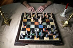 In a photo taken Friday, April 19, 2019, a man poses for The Associated Press at an open-ended chess game he has with his roommate in his home in Plainfield, N.J. The man and his roommate have opposite schedules, so they make their move when it's convenient and use a candlestick to let each other know whose turn is up. The man has cleared his gambling addiction for 22 years by being a member of a 12-step program. He says he has seen the rise in television advertisements for gambling web sites. (AP Photo/Julio Cortez)