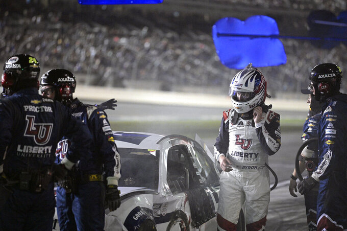 William Byron, second from right, looks on as crew members work on his car on pit road during a NASCAR Cup Series auto race at Daytona International Speedway, Saturday, Aug. 28, 2021, in Daytona Beach, Fla. (AP Photo/Phelan M. Ebenhack)