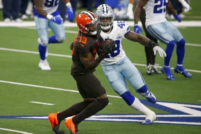 Cleveland Browns wide receiver Odell Beckham Jr. (13) catches a pass in front of Dallas Cowboys' Joe Thomas (48) in the first half of an NFL football game in Arlington, Texas, Sunday, Oct. 4, 2020. (AP Photo/Michael Ainsworth)