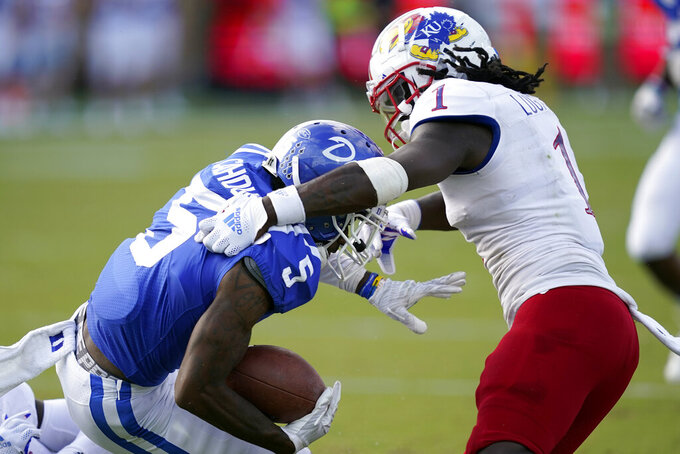Duke wide receiver Jalon Calhoun (5) is tackled by Kansas safety Kenny Logan Jr. (1) during the first half of an NCAA college football game in Durham, N.C., Saturday, Sept. 25, 2021. (AP Photo/Gerry Broome)