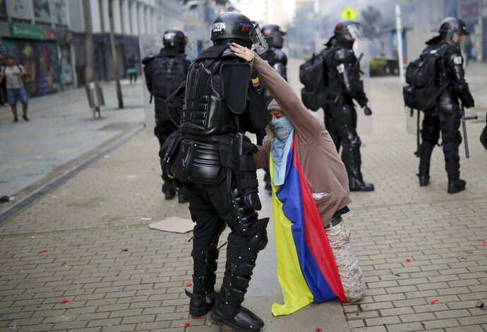 An anti-government protester kneels before a police officer in Bogota, Colombia, Friday, Nov. 22, 2019. Labor unions and student leaders called on Colombians to bang pots and pans on Friday evening in another act of protest while authorities announced three people had died in overnight clashes with police after demonstrations during a nationwide strike. (AP Photo/Ivan Valencia)