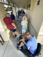People wait in a line in Sarasota, Fla., Thursday morning, Dec. 31, 2020, as COVID-19 vaccinations were made available to those over 65 and high-risk frontline health care workers. (Tom Stathis via AP)