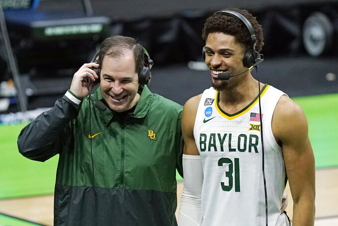 Baylor head coach Scott Drew and MaCio Teague (31) are interviewed after Baylor's win over Hartford in a college basketball game in the first round of the NCAA tournament at Lucas Oil Stadium in Indianapolis Friday, March 19, 2021, in Indianapolis, Tenn. (AP Photo/Mark Humphrey)