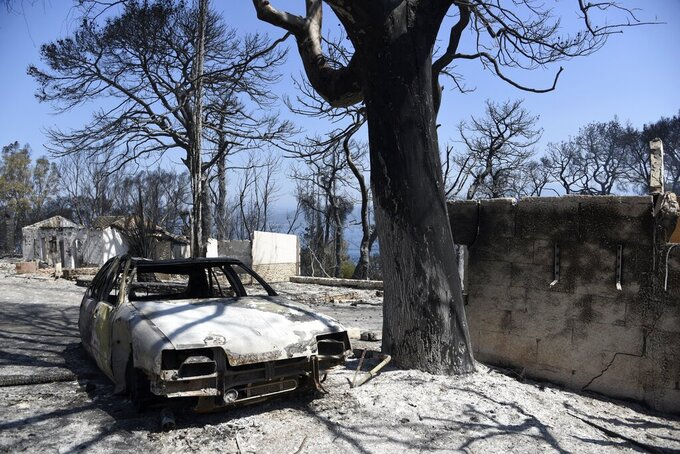 Burned houses and a car after a wildfire in Lampiri village, east of Patras city, Greece, Sunday, Aug. 1, 2021. A wildfire that broke out Saturday in western Greece forced the evacuation of four villages and people on a beach by the Fire Service, the Coast Guard and private boats, authorities said. (AP Photo/Andreas Alexopoulos)