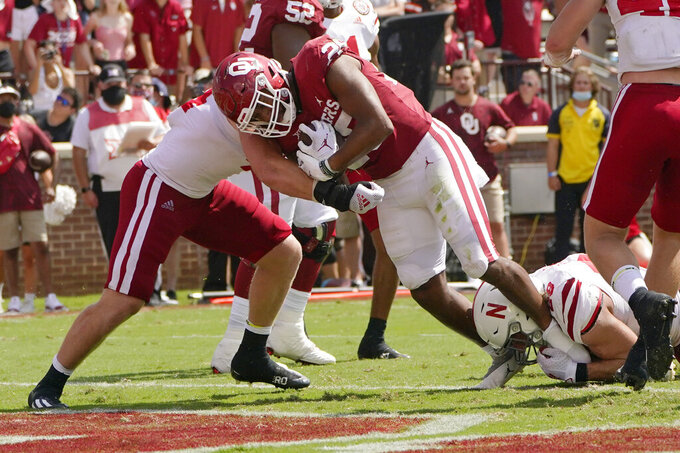 Oklahoma running back Kennedy Brooks pushes into the end zone for a touchdown between Nebraska linebackers Garrett Nelson, left, and Luke Reimer, right, in the second half of an NCAA college football game, Saturday, Sept. 18, 2021, in Norman, Okla. (AP Photo/Sue Ogrocki)