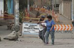 In this Feb. 12, 2020 photo, residents walk past signs that read in Spanish
