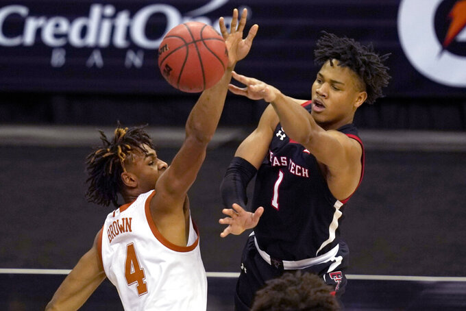 Texas Tech guard Terrence Shannon Jr. (1) passes while covered by Texas forward Greg Brown (4) during the second half of an NCAA college basketball game in the quarterfinal round of the Big 12 men's tournament in Kansas City, Mo., Thursday, March 11, 2021. (AP Photo/Orlin Wagner)