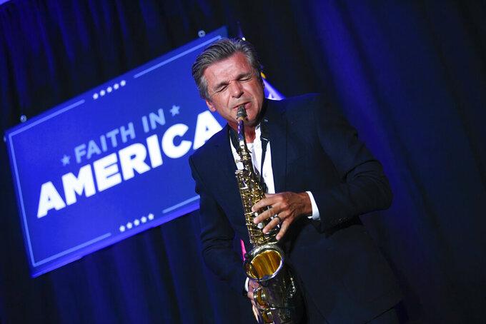 Pastor Jentezen Franklin plays the saxophone during a President Donald Trump campaign event courting devout conservatives by combining praise, prayer and patriotism, Thursday, July 23, 2020, in Alpharetta, Ga. (AP Photo/John Amis)