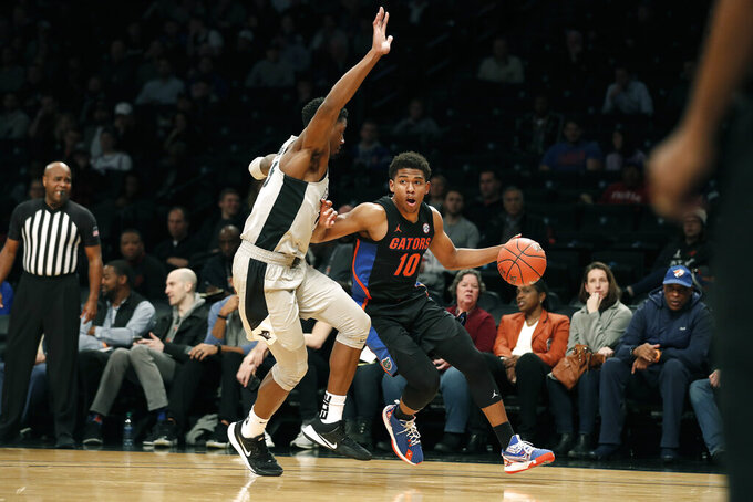 Florida guard Noah Locke (10) drives against Providence forward Emmitt Holt (15) during the first half of an NCAA college basketball game at Barclays Center, Tuesday, Dec. 17, 2019, in New York. (AP Photo/Michael Owens)