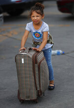 A migrant girl pushes a piece of luggage before she and her family enter the immigration office on the Mexican side of the border, before they are escorted across to apply for asylum on the United States side, in Nuevo Laredo, Mexico, Wednesday, July 17, 2019. Asylum-seekers grappled to understand what a new U.S. policy that all but eliminates refugee claims by Central Americans and many others meant for their bids to find a better life in America amid a chaos of rumors, confusion and fear. (AP Photo/Marco Ugarte)