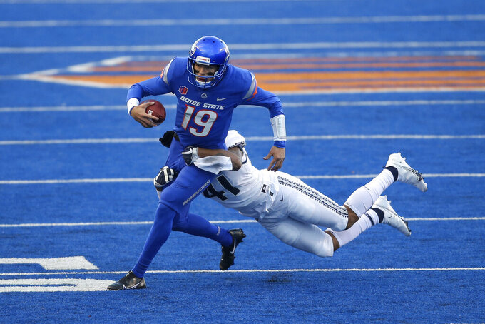 Boise State quarterback Hank Bachmeier (19) is wrapped up on a scramble by Utah State linebacker Elijah Shelton (41) in the first half of an NCAA college football game Saturday, Oct. 24, 2020, in Boise, Idaho. Boise State won 42-13. (AP Photo/Steve Conner)