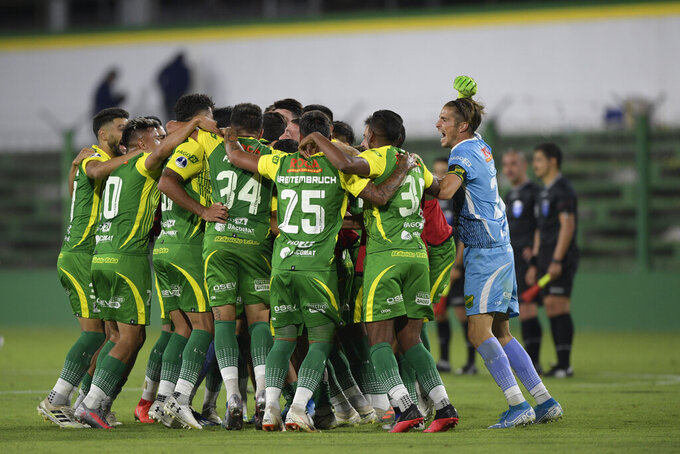 Players of Argentina's Defensa y Justicia celebrate at the end of a Copa Sudamericana quarterfinal second leg soccer match at Norberto Tomaghello stadium in Buenos Aires, Argentina, Wednesday, Dec. 16, 2020. Defensa y Justicia won 4-2 on aggregate and advances for the semifinals. (Juan Mabromata/Pool via AP)
