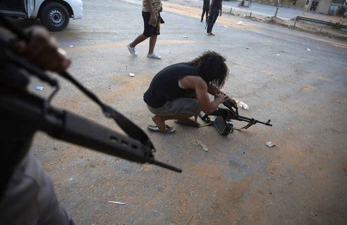 FILE - In this Sept. 21, 2018 file photo, a fighter under the UN-backed government prepares his gun during clashes in southern Tripoli, Libya. Various militias, many of which are little more than criminal gangs, are mobilizing to fight over the capital, Tripoli after forces led by self-styled Libyan National Army, led by Field Marshal Khalifa Hifter, launched a surprise offensive to retake Tripoli on April 5, 2019, from the transitional government supported by U.N. and Western nations led by Fayez Sarraj. Hifter's opponents view him as an aspiring dictator. (AP Photo/Mohamed Ben Khalifa, File)