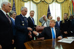 President Donald Trump hands a pen to Air Force Gen. Paul Selva after signing