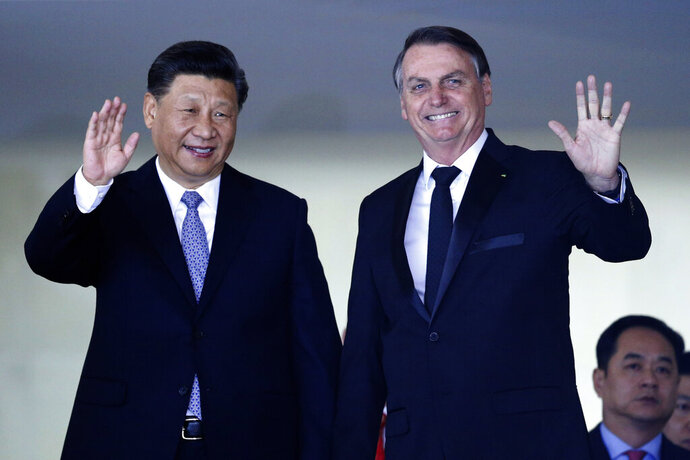 China's President Xi Jinping, left, and Brazil's President Jair Bolsonaro wave to reporters upon Xi Jinping's arrival for a bilateral meeting on the sidelines of the 11th edition of the BRICS Summit, at the Itamaraty Palace, in Brasília, Brazil, Wednesday, Nov. 13, 2019. (AP Photo/Eraldo Peres)