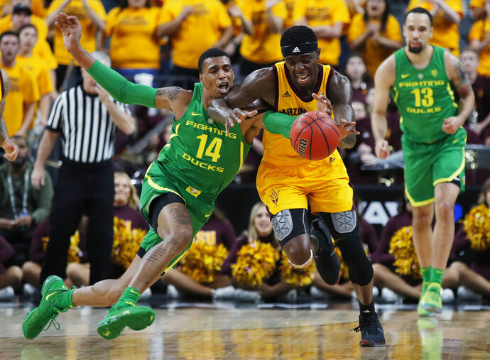 Oregon's Kenny Wooten (14) tries to steal the ball from Arizona State's Zylan Cheatham during the first half of an NCAA college basketball game in the semifinals of the Pac-12 men's tournament Friday, March 15, 2019, in Las Vegas. (AP Photo/John Locher)