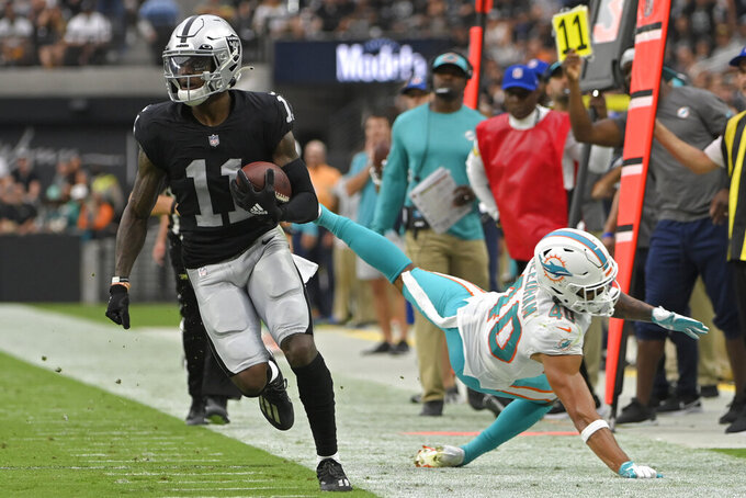 Las Vegas Raiders wide receiver Henry Ruggs III (11) avoids a tackle by Miami Dolphins defensive back Nik Needham (40) during the first half of an NFL football game, Sunday, Sept. 26, 2021, in Las Vegas. (AP Photo/David Becker)