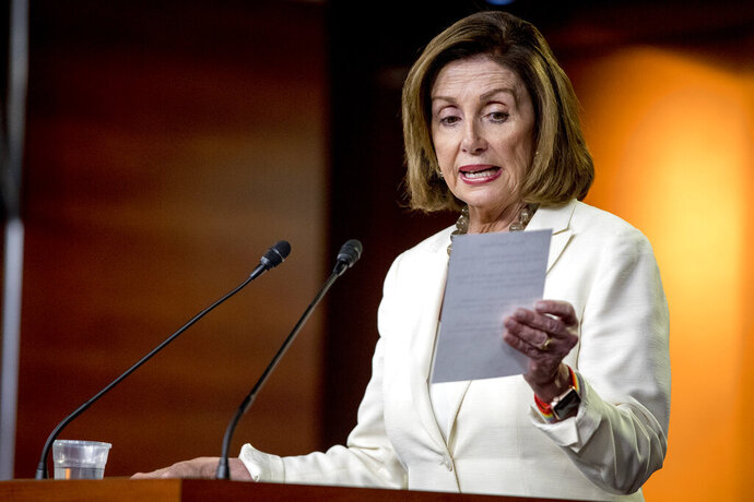 House Speaker Nancy Pelosi of Calif. reads from a paper titled