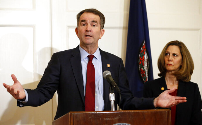 In this Feb. 2, 2019, photo, Virginia Gov. Ralph Northam, left, accompanied by his wife, Pam, speaks during a news conference in the governor's mansion in Richmond, Va. Democrats are hoping there's a silver lining to the Northam mess - that it shows they won't tolerate racism. Every level of the party has condemned the Democratic Virginia governor and demanded he step down. That follows disclosure that his medical school yearbook page features photos of a man in blackface standing with someone dressed in Klu Klux Klan attire.(AP Photo/Steve Helber)