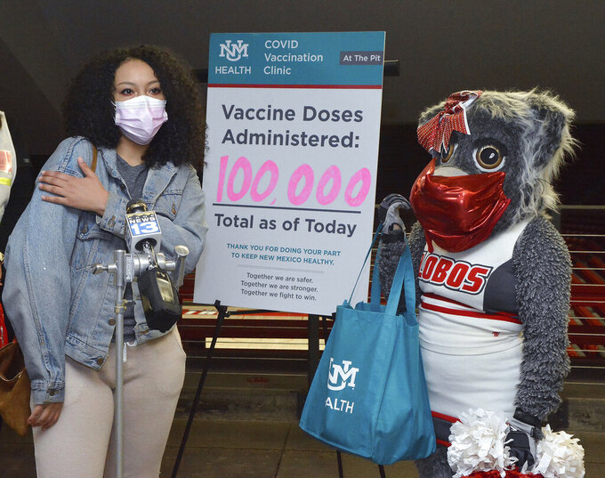 """Kiara Herzer, of Albuquerque, stands with University of New Mexico mascot """"Lucy Lobo"""" as she tells how she got her second vaccine shot in her right arm as she was the 100,000th COVID-19 vaccine shot administered at the UNM Health vaccination clinic at the Pit, Wednesday, April, 28 , 2021, in Albuquerque, N.M.(Jim Thompson/The Albuquerque Journal via AP)"""