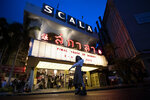 A woman poses beneath the cinema marquee of the Scala theater in Friday, July 3, 2020 in Bangkok, Thailand. The Scala theater has shut its doors after 51 years as a shrine for Thai movie-goers. (AP Photo/Sakchai Lalit)