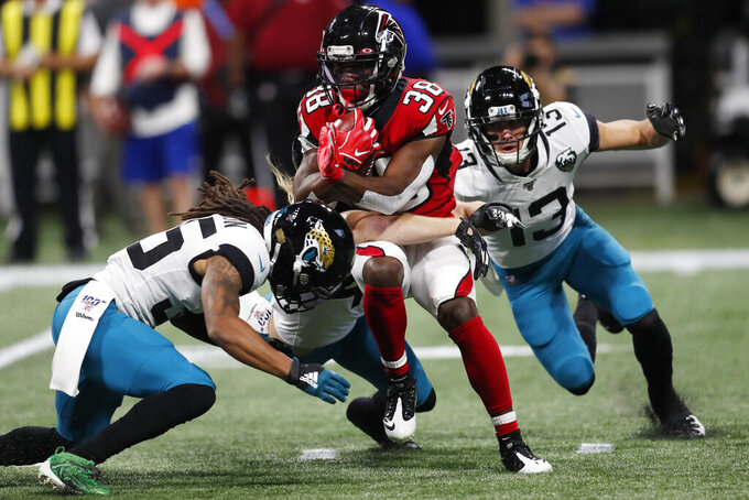 Atlanta Falcons running back Kenjon Barner (38) runs against Jacksonville Jaguars wide receiver Michael Walker (13) on a kickoff return during the first half of an NFL football game, Sunday, Dec. 22, 2019, in Atlanta. (AP Photo/John Bazemore)