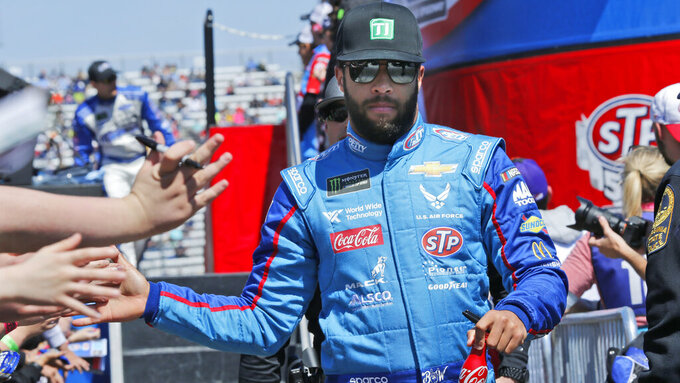 NASCAR Cup Series driver Bubba Wallace (43) greets fans during driver introductions prior to the NASCAR Cup Series auto race at the Martinsville Speedway in Martinsville, Va., Sunday, March 24, 2019. (AP Photo/Steve Helber)