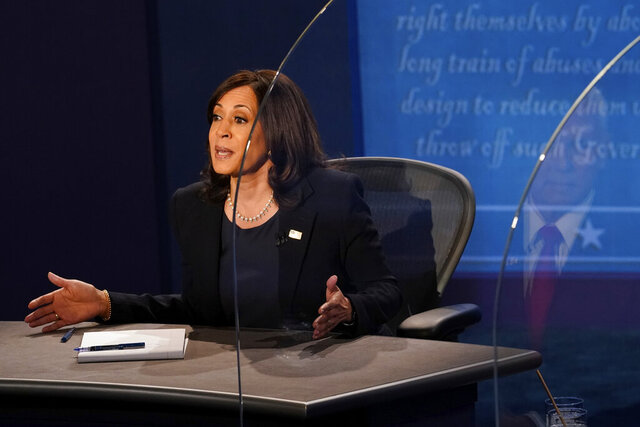 Vice President Mike Pence is reflected in the plexiglass barrier as Democratic vice presidential candidate Sen. Kamala Harris, D-Calif., answers a question during the vice presidential debate Wednesday, Oct. 7, 2020, at Kingsbury Hall on the campus of the University of Utah in Salt Lake City. (AP Photo/Morry Gash, Pool)