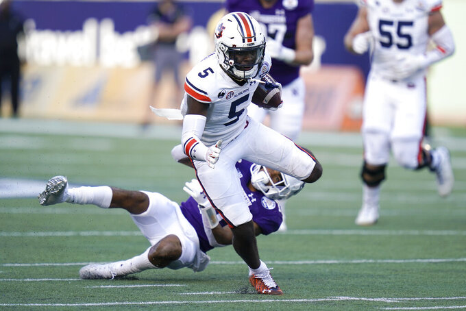 Auburn wide receiver Kobe Hudson (5) runs for yardage past Northwestern defensive back Cameron Ruiz during the second half of the Citrus Bowl NCAA college football game, Friday, Jan. 1, 2021, in Orlando, Fla. Northwestern beat Auburn 35-19. (AP Photo/John Raoux)