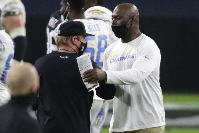 Las Vegas Raiders head coach Jon Gruden, left, and Los Angeles Chargers head coach Anthony Lynn shake hands after an NFL football game, Thursday, Dec. 17, 2020, in Las Vegas. (AP Photo/Isaac Brekken)