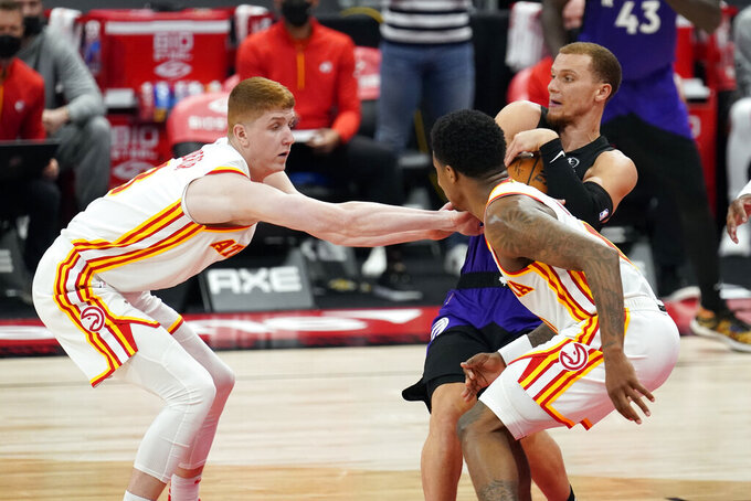 Toronto Raptors guard Malachi Flynn (8) grabs the ball away from Atlanta Hawks guard Kevin Huerter (3) and guard Brandon Goodwin (0) during the second half of an NBA basketball game Tuesday, April 13, 2021, in Tampa, Fla. (AP Photo/Chris O'Meara)