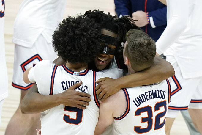 Illinois's Ayo Dosunmu hugs Andre Curbelo (5) and Tyler Underwood (32) after Illinois defeated Ohio State in overtime of an NCAA college basketball championship game at the Big Ten Conference tournament, Sunday, March 14, 2021, in Indianapolis. Illinois won in overtime. (AP Photo/Darron Cummings)