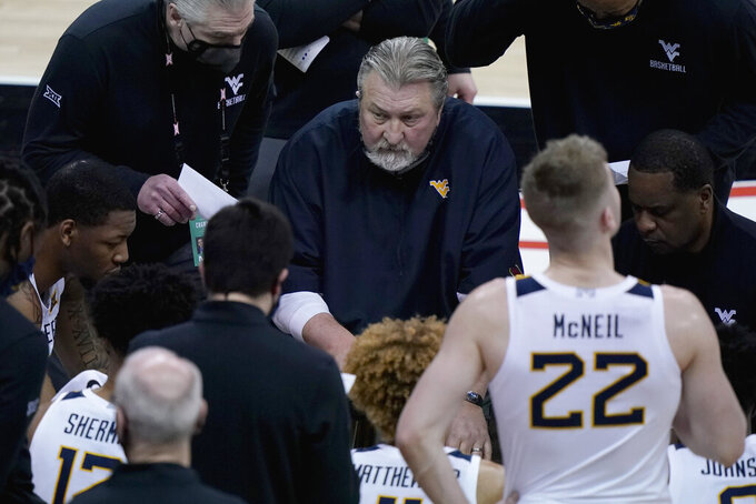 West Virginia head coach Bob Huggins talks to his players during a timeout in the second half of an NCAA college basketball game against Oklahoma State in the second round of the Big 12 men's tournament in Kansas City, Mo., Thursday, March 11, 2021. Oklahoma State won 72-69. (AP Photo/Charlie Riedel)