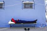 An Afghan refugee rests in an Italian Red Cross refugee camp, in Avezzano, Italy, Tuesday, Aug. 31, 2021. This quarantine camp in Abruzzo, central Italy, where 1,250 migrants are hosted, is expected to close in a week as the quarantine expires and they are moved to other structures to apply for asylum. (AP Photo/Andrew Medichini)