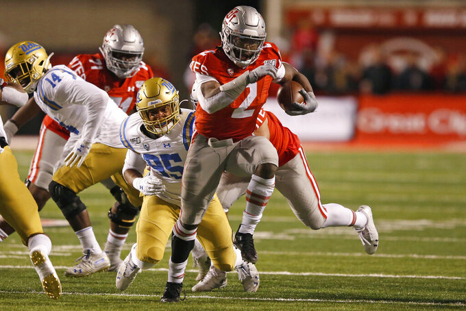 Utah running back Zack Moss (2) out runs UCLA linebacker Jason Harris (95) in the first half during an NCAA college football game Saturday, Nov. 16, 2019, in Salt Lake City. (AP Photo/Rick Bowmer)