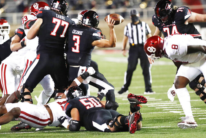Texas Tech quarterback Henry Colombi gets a pass off under pressure from Oklahoma defenders during the first half of an NCAA college football game Saturday, Oct. 31, 2020, in Lubbock, Texas. (AP Photo/Mark Rogers)