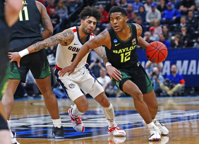 Baylor guard Jared Butler (12) drives around Gonzaga guard Josh Perkins, left, during the first half of a second-round game in the NCAA men's college basketball tournament Saturday, March 23, 2019, in Salt Lake City. (AP Photo/Rick Bowmer)