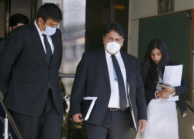 Faisal Siddiqi, center, a lawyer for the family of Daniel Pearl, an American reporter who was kidnapped and killed in Pakistan in 2002, leaves the Supreme Court with his team after an appeal hearing in Islamabad, Pakistan, Tuesday, Dec. 1, 2020. Pakistan's top court on Tuesday resumed the hearing of an appeal from the family of Pearl against the acquittal of a British-born Pakistani man convicted over the beheading of the Wall Street Journal reporter.  (AP Photo/Anjum Naveed)
