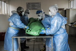 """Members of the Saaberie Chishty Burial Society prepare the body of a person who died from COVID-19 at the Avalon Cemetery in Lenasia, Johannesburg Saturday Dec. 26, 2020. South Africa's health minister has announced an """"alarming rate of spread"""" in the country, with more than 14,000 new confirmed coronavirus cases and more than 400 deaths reported Wednesday. It was the largest single-day increase in cases. (AP Photo/Shiraaz Mohamed)"""